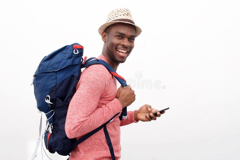 Homem afro-americano considerável com chapéu e smartphone da terra arrendada do saco contra o fundo branco imagens de stock