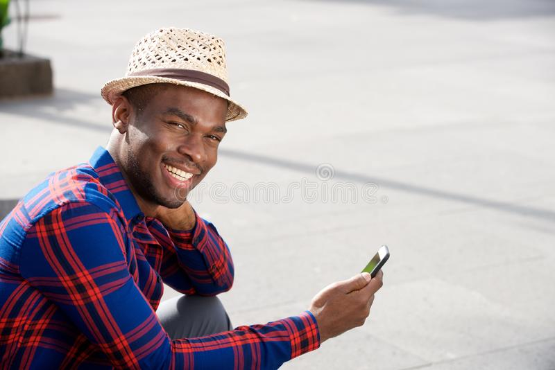 Homem afro-americano considerável com o smartphone da terra arrendada do chapéu imagem de stock