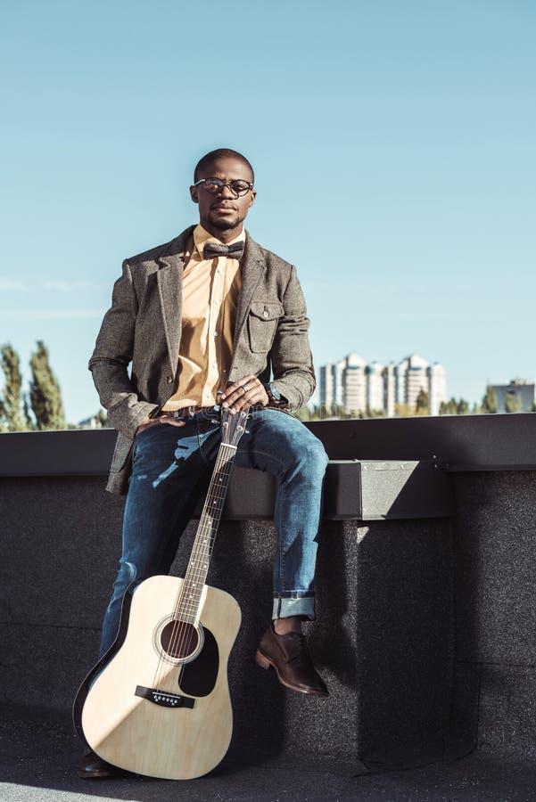 Homem afro-americano considerável no revestimento e nos vidros de mistura de lã, sentando-se no telhado imagem de stock royalty free