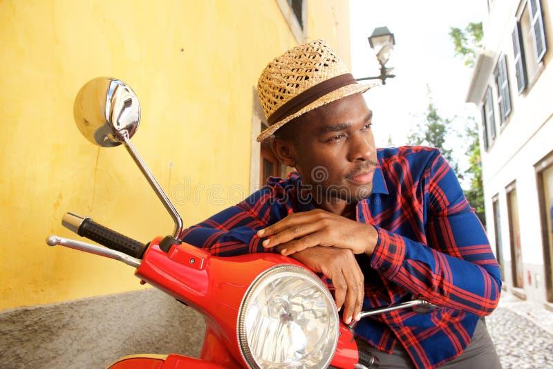 Homem afro-americano considerável que inclina-se no 'trotinette' fora fotos de stock royalty free
