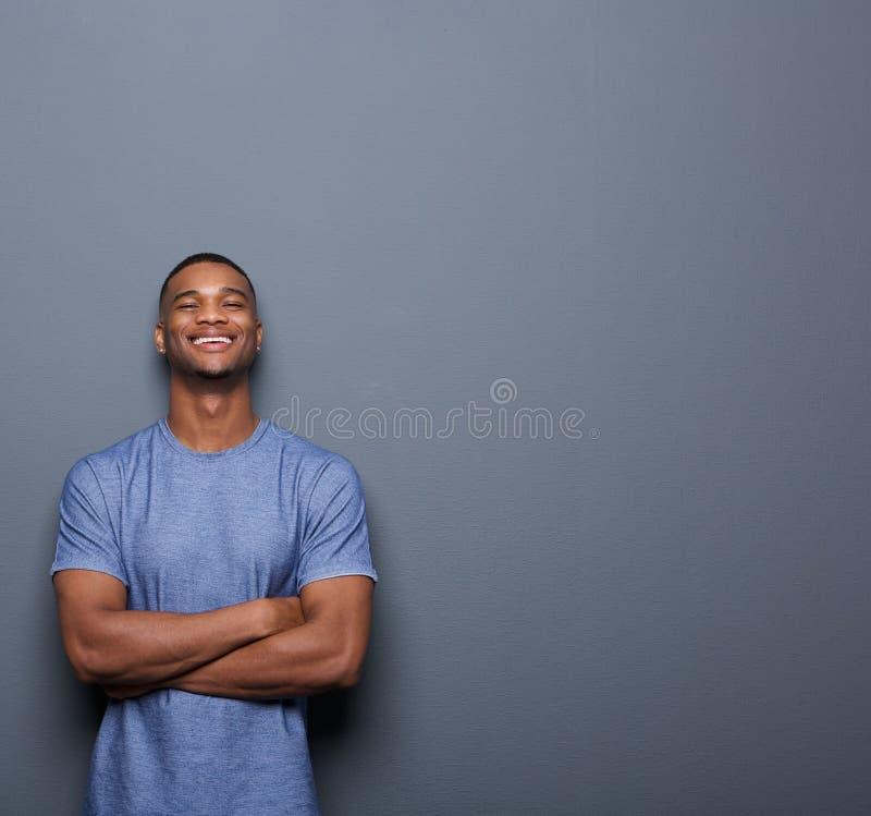 Homem afro-americano considerável que ri com os braços cruzados fotografia de stock royalty free
