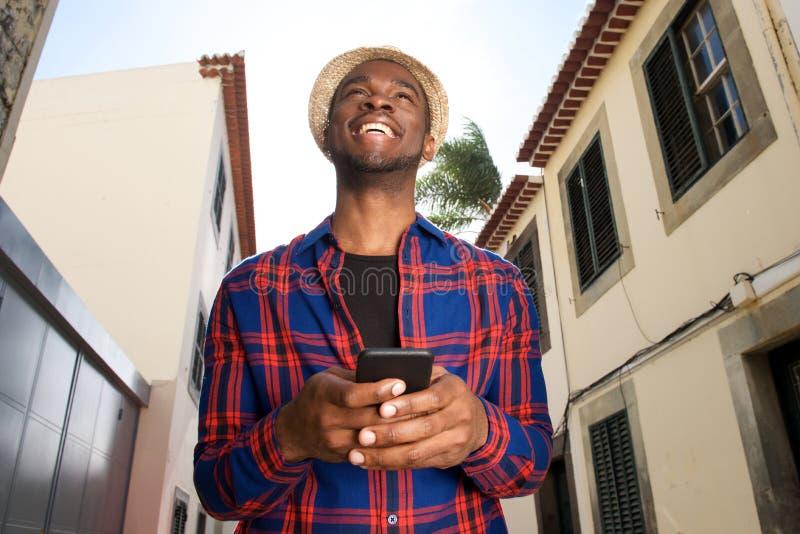 Homem afro-americano considerável que sorri com telefone celular fora na cidade imagens de stock royalty free