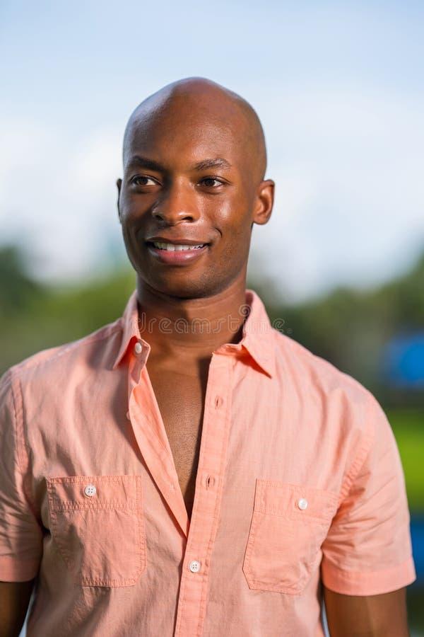 Homem afro-americano considerável que sorri fora da câmera Homem da foto tomado fora com fundo obscuro fotos de stock