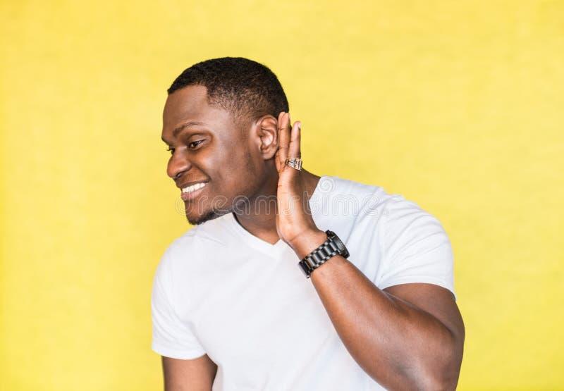 Homem afro-americano consider?vel novo que tenta ouvir melhor unindo sua palma ? orelha fotografia de stock