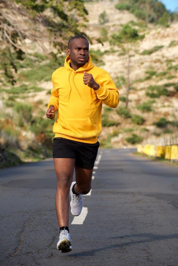 Homem afro-americano da aptidão do corpo completo que corre na rua fotos de stock
