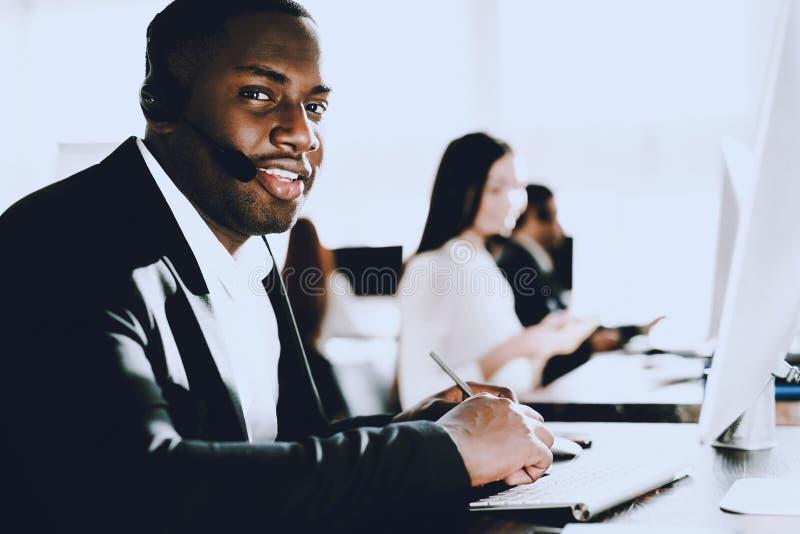 Homem afro-americano de assento que trabalha no centro de atendimento Gerente com computador homem no local de trabalho Consultan fotos de stock