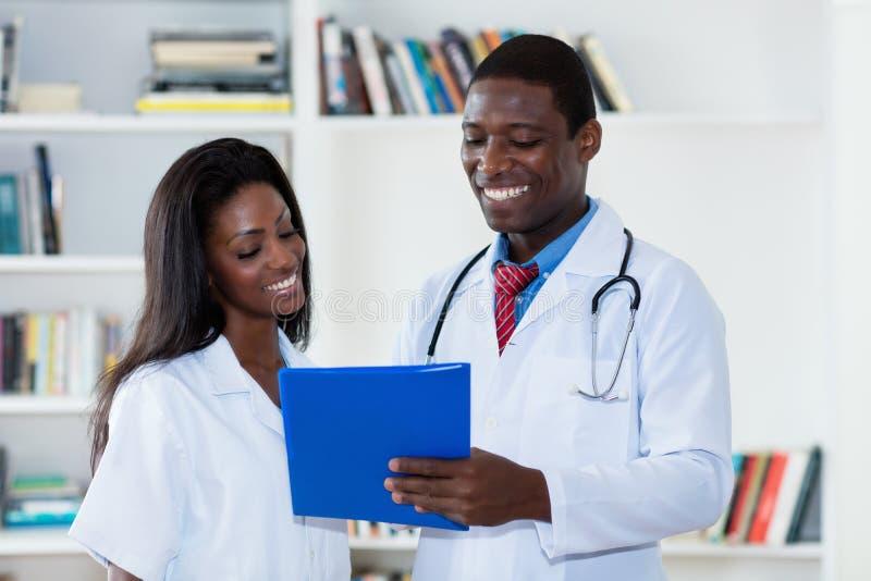 Homem afro-americano de riso e doutor fêmea fotografia de stock