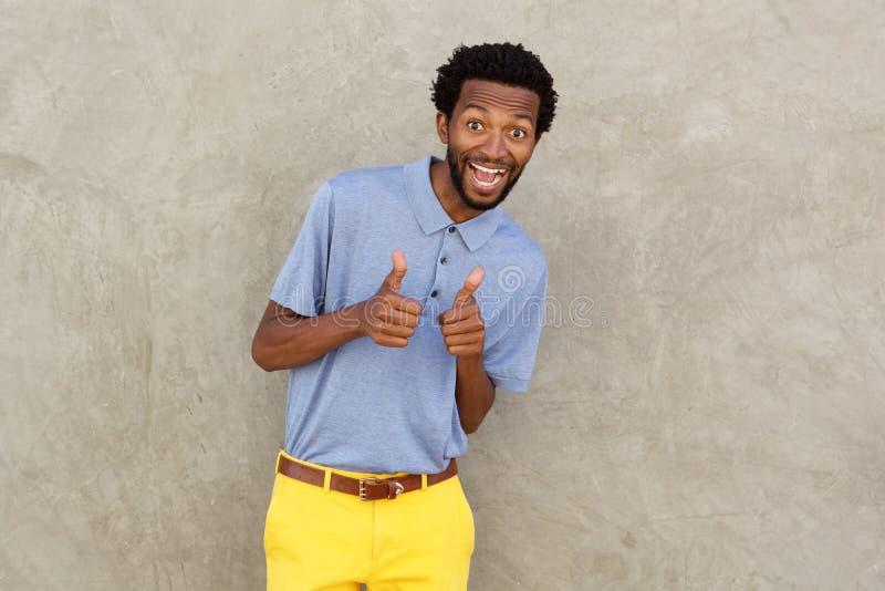 Homem afro-americano de sorriso com ambos os polegares acima imagens de stock royalty free