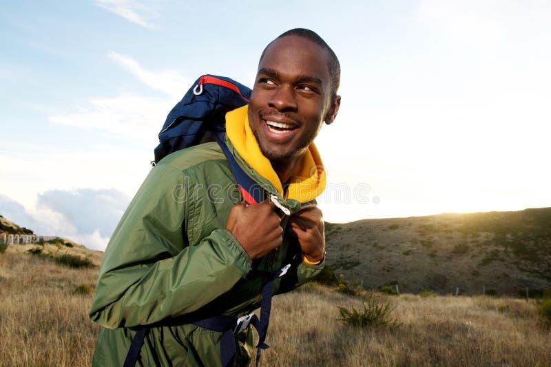 Homem afro-americano de sorriso com a trouxa que caminha nas montanhas foto de stock royalty free