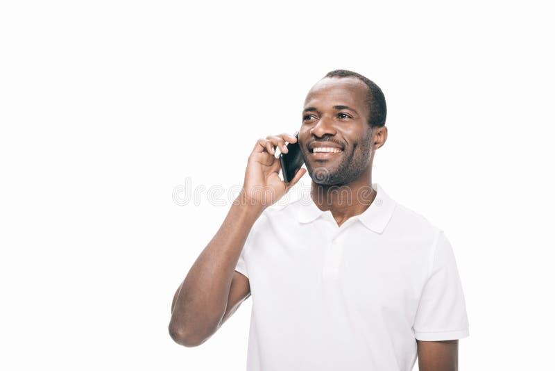 homem afro-americano de sorriso considerável que fala no smartphone foto de stock