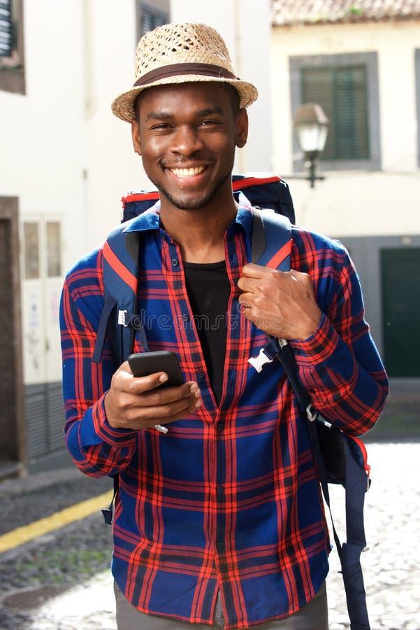 Homem afro-americano de sorriso do curso com trouxa e telefone celular imagens de stock