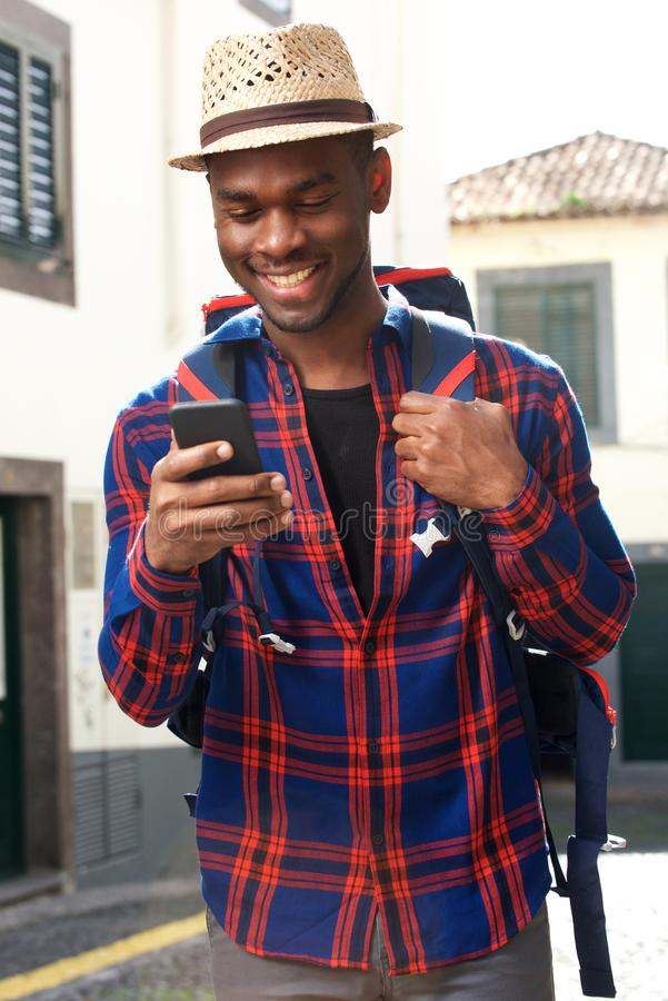Homem afro-americano de sorriso do curso com trouxa e telefone celular imagem de stock