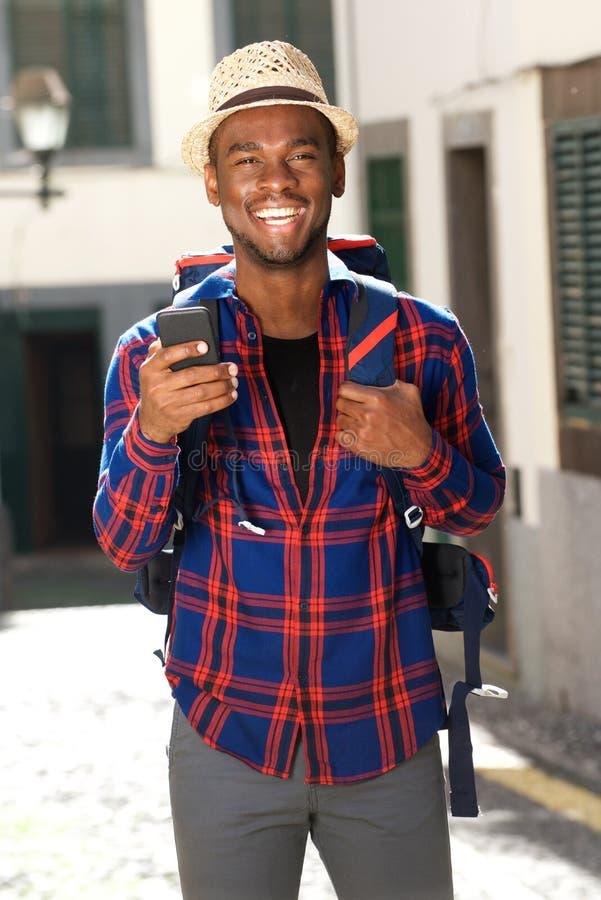 Homem afro-americano de sorriso do curso com trouxa e telefone imagens de stock