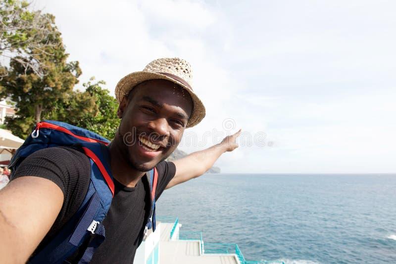 Homem afro-americano de sorriso do curso que toma o selfie o mar e apontar o dedo imagens de stock royalty free