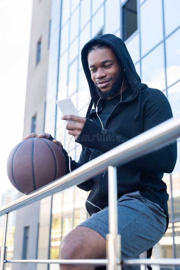homem afro-americano de sorriso nos fones de ouvido usando o smartphone ao guardar a bola do basquetebol imagem de stock