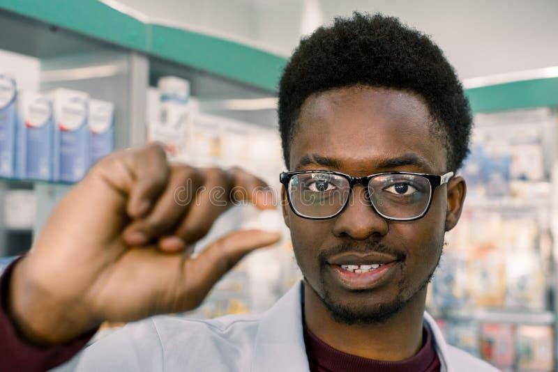 Homem afro-americano de sorriso novo do farmacêutico do doutor que guarda o comprimido branco na mão, close-up da tabuleta Foco n imagem de stock