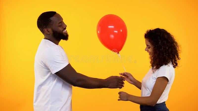 Homem afro-americano de sorriso que apresenta o bal?o ? mulher bonito, presente de anivers?rio, data imagem de stock royalty free