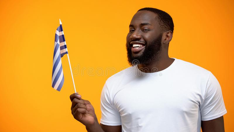 Homem afro-americano de sorriso que guarda a bandeira de Gr?cia, amizade internacional imagem de stock royalty free