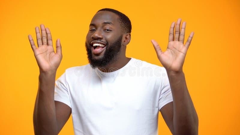 Homem afro-americano de sorriso que mostra as palmas abertas, dando acima, fundo amarelo fotografia de stock