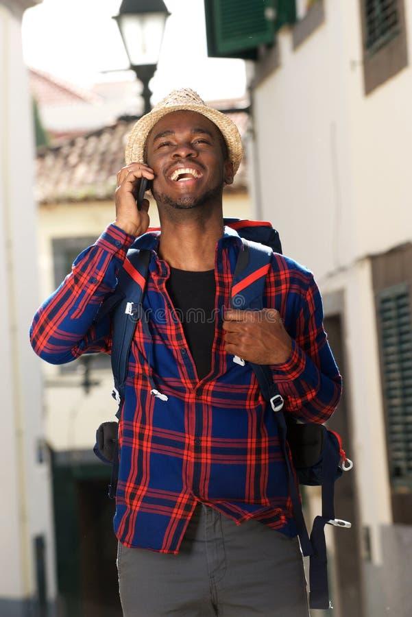 Homem afro-americano do curso que sorri com trouxa e que fala no telefone celular imagem de stock royalty free
