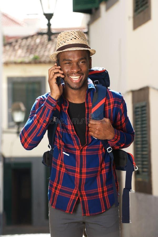 Homem afro-americano do curso que sorri com trouxa e que fala com telefone celular fotos de stock