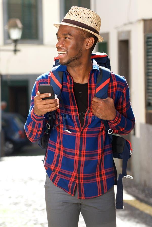 Homem afro-americano do curso que sorri com trouxa e telefone celular imagens de stock royalty free