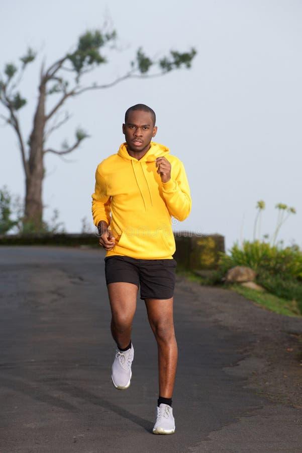 Homem afro-americano do exercício do corpo completo que corre na rua imagens de stock