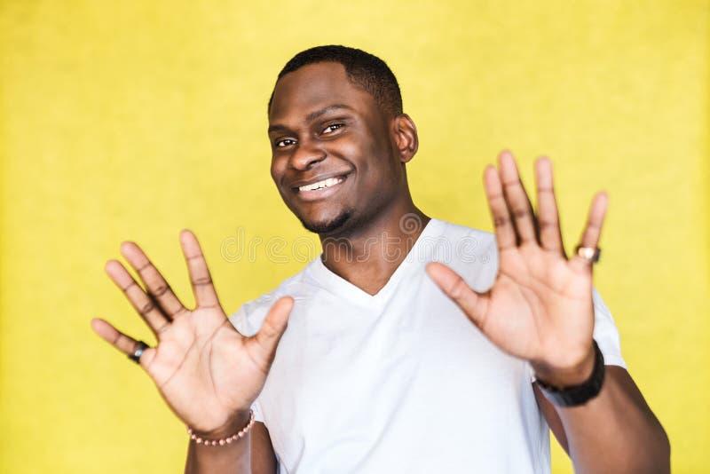 Homem afro-americano do retrato, levantando as palmas no nenhum ou o gesto da parada, sorrindo inabilmente, querendo diminuir a o imagens de stock