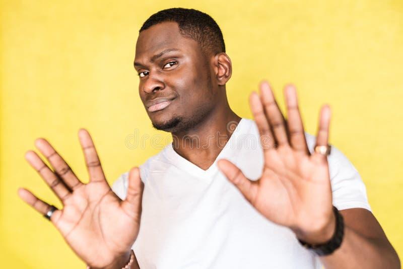 Homem afro-americano do retrato, levantando as palmas no nenhum ou o gesto da parada, sorrindo inabilmente, querendo diminuir a o imagens de stock royalty free