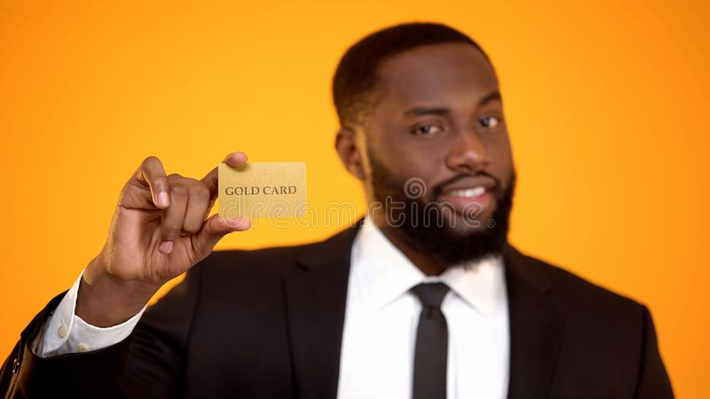 Homem afro-americano elegante no terno formal que mostra o cart?o do ouro, sociedade do clube imagens de stock