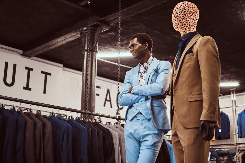 Homem afro-americano elegantemente vestido que levanta com os braços cruzados perto do manequim em uma loja clássica do menswear fotografia de stock royalty free