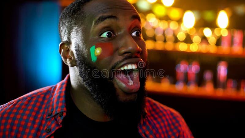 Homem afro-americano extremamente emocional chocado com vitória portuguesa na competição fotografia de stock royalty free