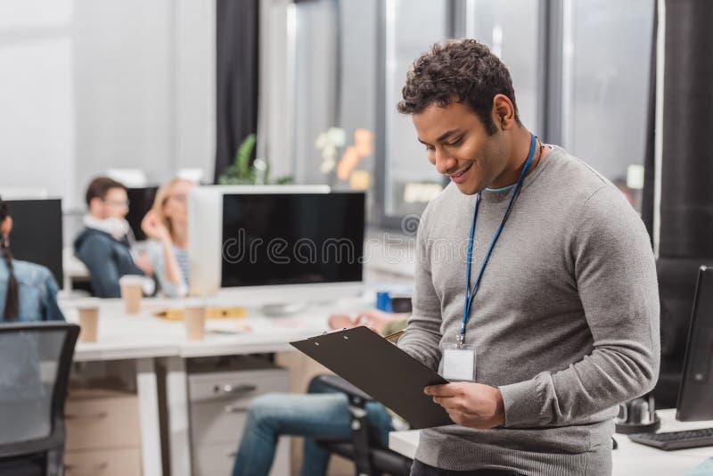 homem afro-americano feliz com escrita da etiqueta do nome algo no planchette fotografia de stock royalty free