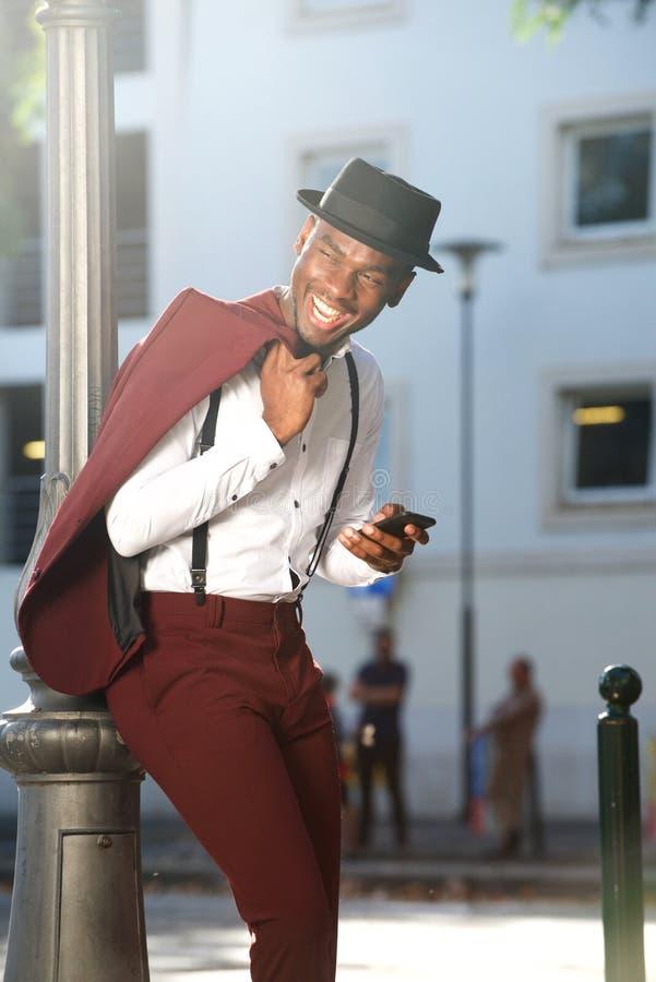 Homem afro-americano feliz com terno do vintage e telefone celular na cidade fotografia de stock
