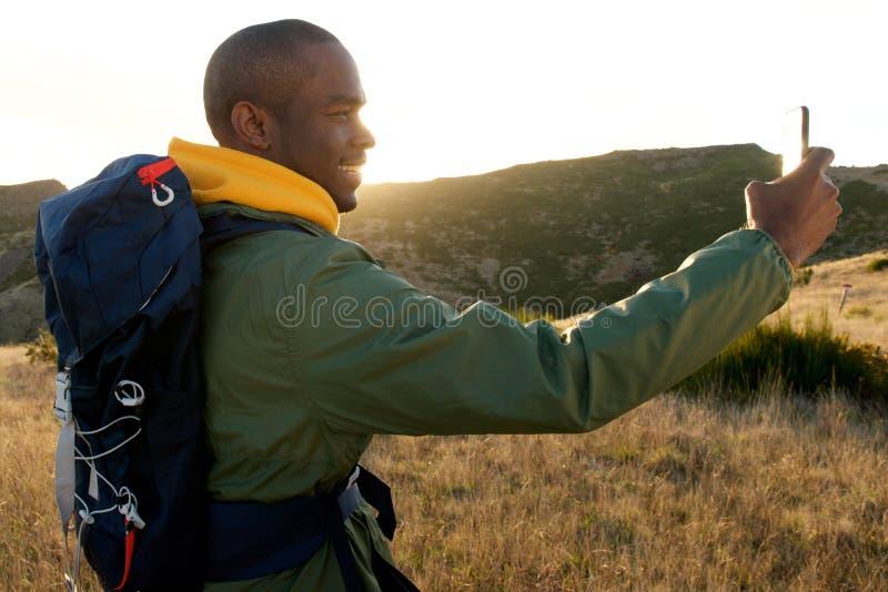 Homem afro-americano feliz com a trouxa que toma o selfie durante a caminhada na natureza foto de stock royalty free