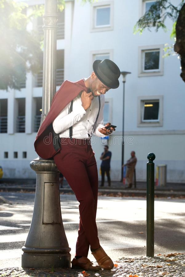 Homem afro-americano feliz do corpo completo no terno que sorri com o telefone celular na cidade fotografia de stock royalty free