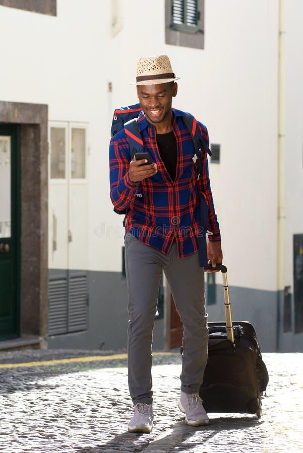 Homem afro-americano feliz do curso do comprimento completo que anda com sacos e telefone celular na rua imagem de stock