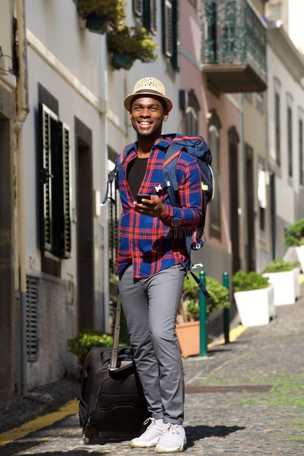 Homem afro-americano feliz do curso do comprimento completo que anda com sacos e telefone celular na rua fotografia de stock