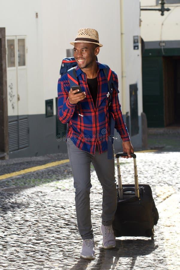 Homem afro-americano feliz do curso do corpo completo que anda com sacos e telefone celular na rua foto de stock royalty free