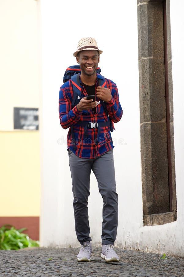 Homem afro-americano feliz do curso do corpo completo que anda com trouxa e telefone celular na rua fotografia de stock
