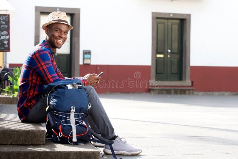 Homem afro-americano feliz do curso do corpo completo que relaxa com telefone celular e saco na rua foto de stock
