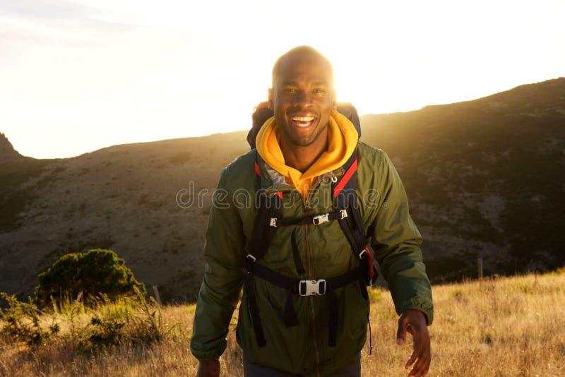 Homem afro-americano feliz que anda dentro com a trouxa nas montanhas e no por do sol no fundo foto de stock