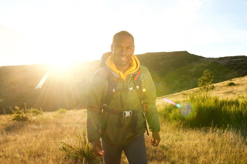 Homem afro-americano feliz que anda na natureza com trouxa e por do sol no fundo imagem de stock