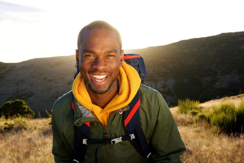Homem afro-americano feliz que anda nas montanhas durante o nascer do sol fotos de stock royalty free