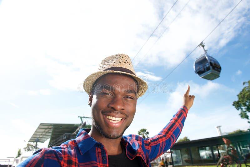 Homem afro-americano feliz que aponta o dedo ao teleférico fotografia de stock royalty free