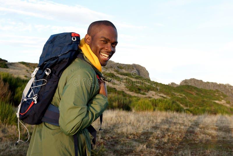 Homem afro-americano feliz que caminha com a trouxa nas montanhas fotos de stock royalty free