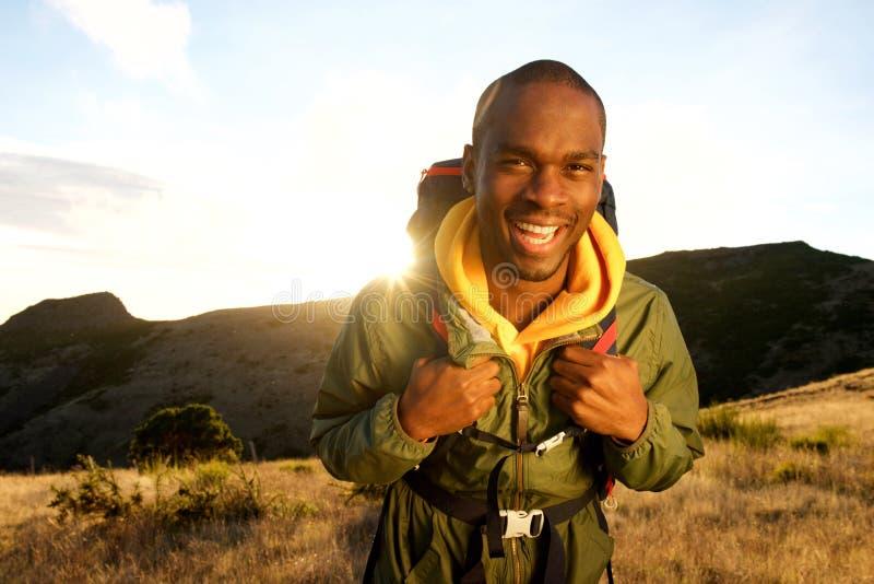 Homem afro-americano feliz que caminha nas montanhas com trouxa e por do sol no fundo fotos de stock