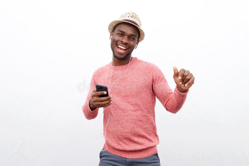 Homem afro-americano feliz que escuta a música com fones de ouvido e telefone celular contra o fundo branco imagens de stock royalty free