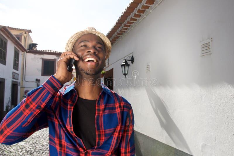 Homem afro-americano feliz que fala no telefone celular fora na cidade foto de stock