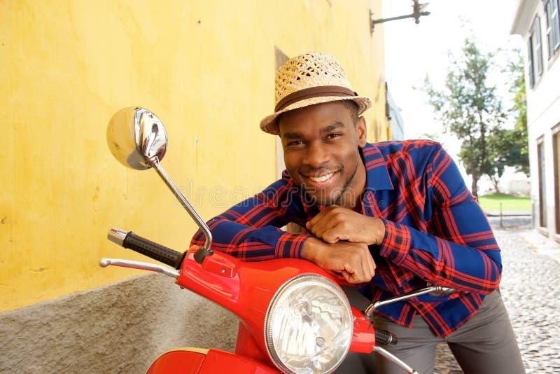 Homem afro-americano feliz que inclina-se no 'trotinette' de motor imagem de stock royalty free